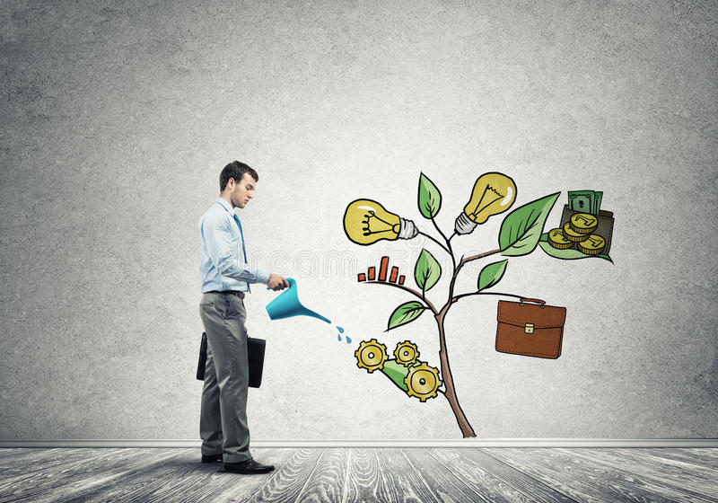 Young businessman in empty room watering drawn growth concept with can. Handsome businessman presenting investment and financial growth concept royalty free stock image