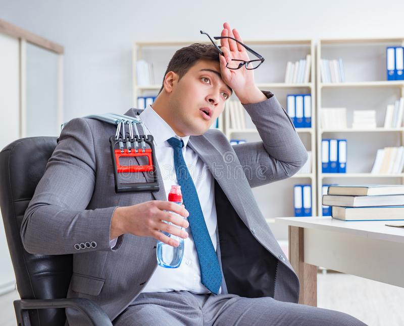 Young businessman exercising with elastic expander in office stock photos