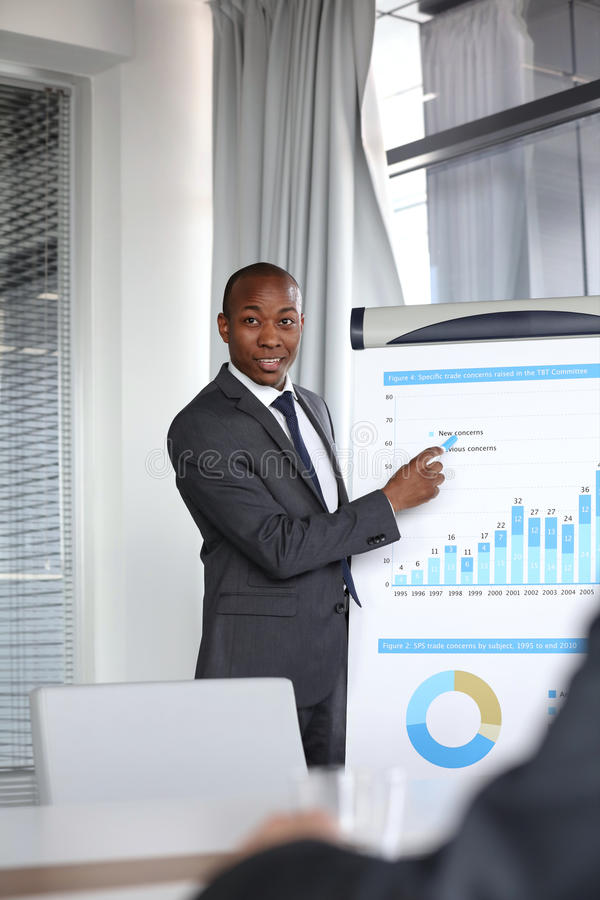 Young businessman explaining graph while giving presentation in board room.  royalty free stock image