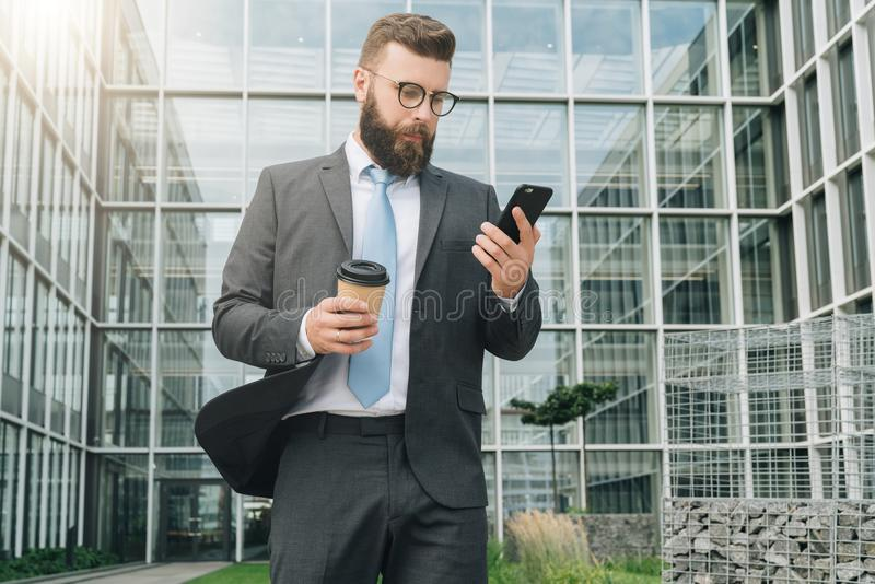 Young businessman in eyeglasses, suit and tie is standing outdoor,using smartphone and drinking coffee. royalty free stock image