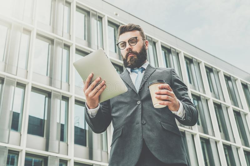 Young businessman in eyeglasses, suit and tie is standing outdoor, using tablet computer and drinking coffee. stock photography