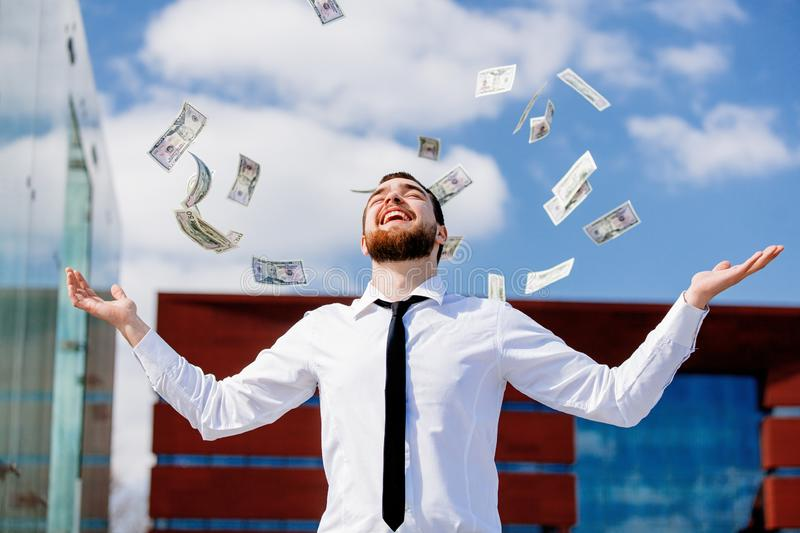 Young businessman with falling cash money royalty free stock photography
