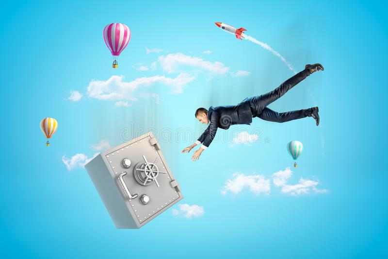 Young businessman falling down in blue sky trying to catch big metal safe, with hot air balloons and rocket in. Background. Business and finance. Earning money stock images