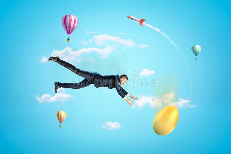 Young businessman falling down in blue sky trying to catch golden egg, with hot air balloons and rocket in background. stock photo