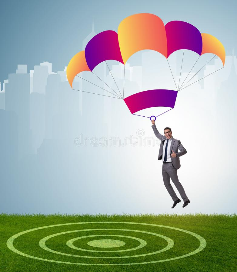 Young businessman falling on parachute in business concept stock images