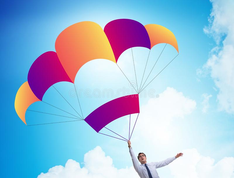 Young businessman falling on parachute in business concept. The young businessman falling on parachute in business concept stock images