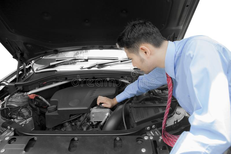 Young businessman fixing a broken car. Picture of young businessman fixing a broken car engine, isolated on white background royalty free stock images