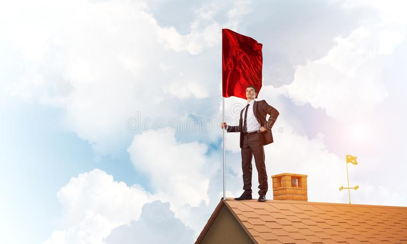 Young businessman with flag presenting concept of leadership. Mixed media stock images