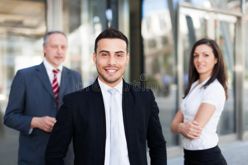 Young businessman in front of a group of business people outdoor stock photography