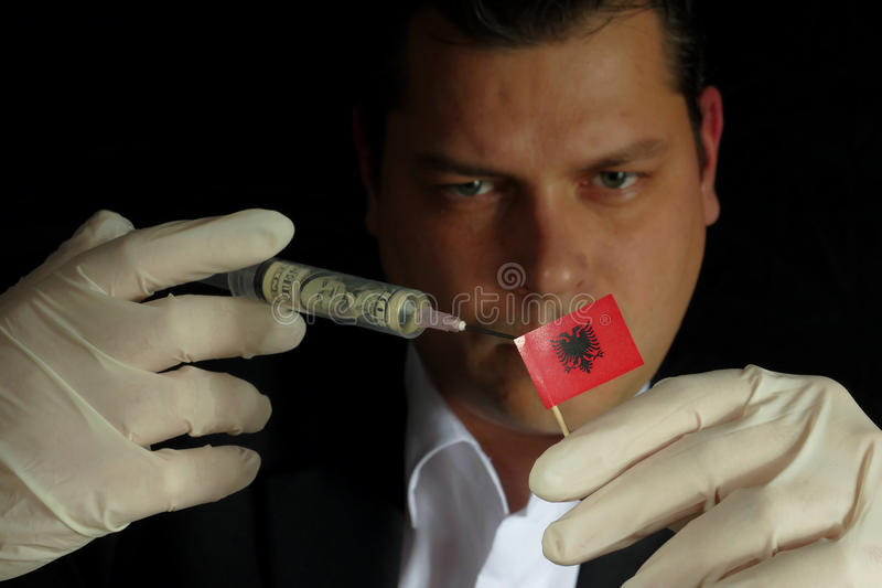 Young businessman gives a financial injection to Albanian flag stock images