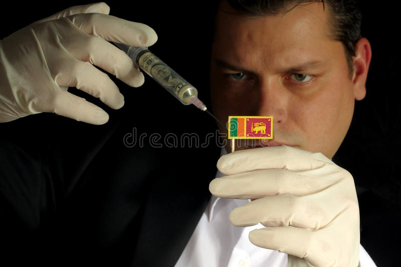 Young businessman gives a financial injection to Sri Lankan flag royalty free stock photo