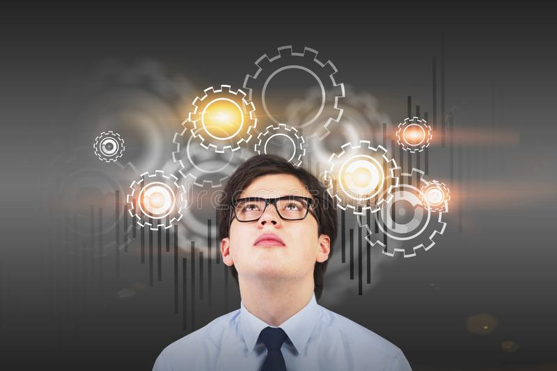 Businessman in glasses looking at gears. Young businessman in glasses looking at gears and graph drawn on gray wall. Concept of brainstorming. Toned image royalty free stock photos