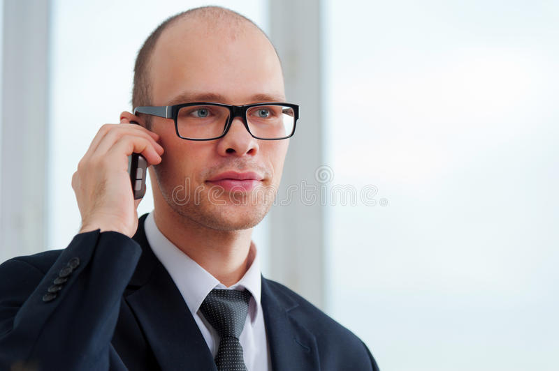 Young businessman with glasses talking on the phone royalty free stock photo