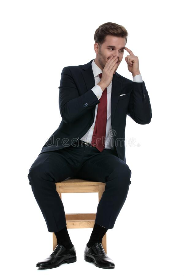 Young businessman gossipping and pointing finger to temple stock images