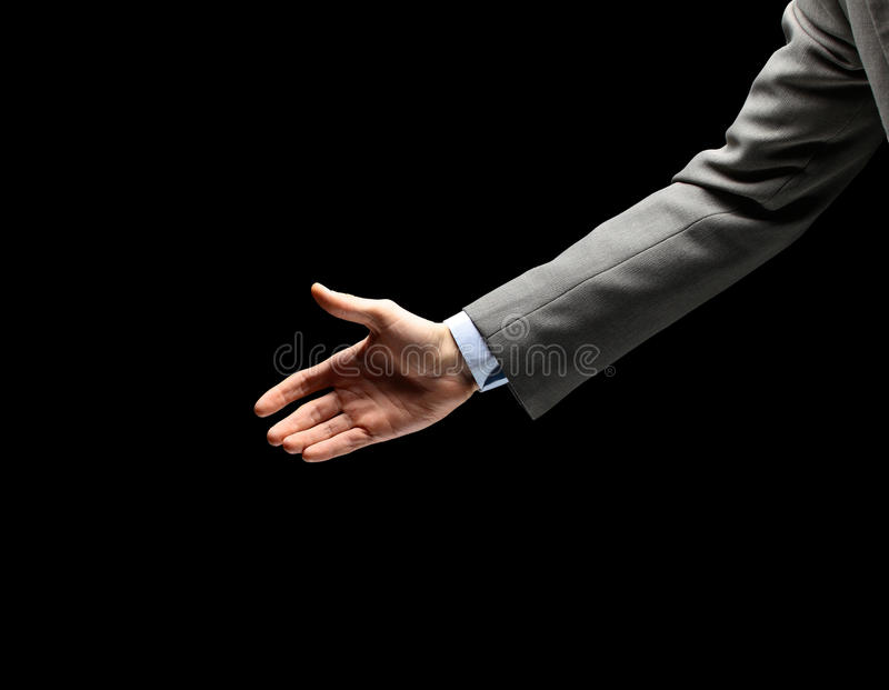 Young businessman greeting. With handshake isolated on black stock image