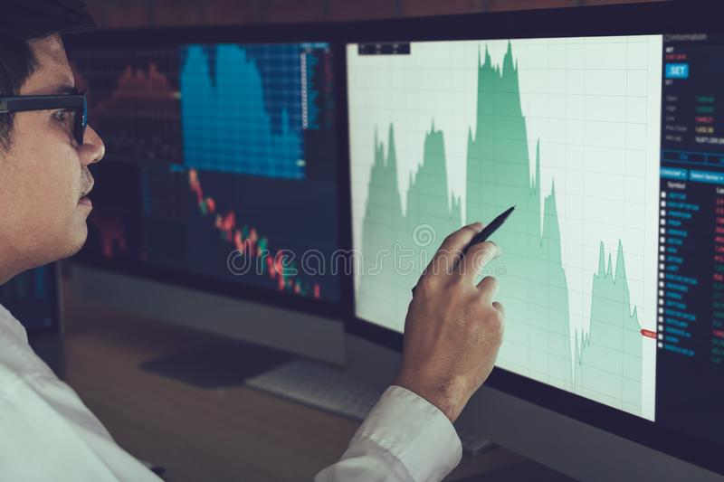 Young businessman hand pointing to stock market chart on computer screen.  royalty free stock photos