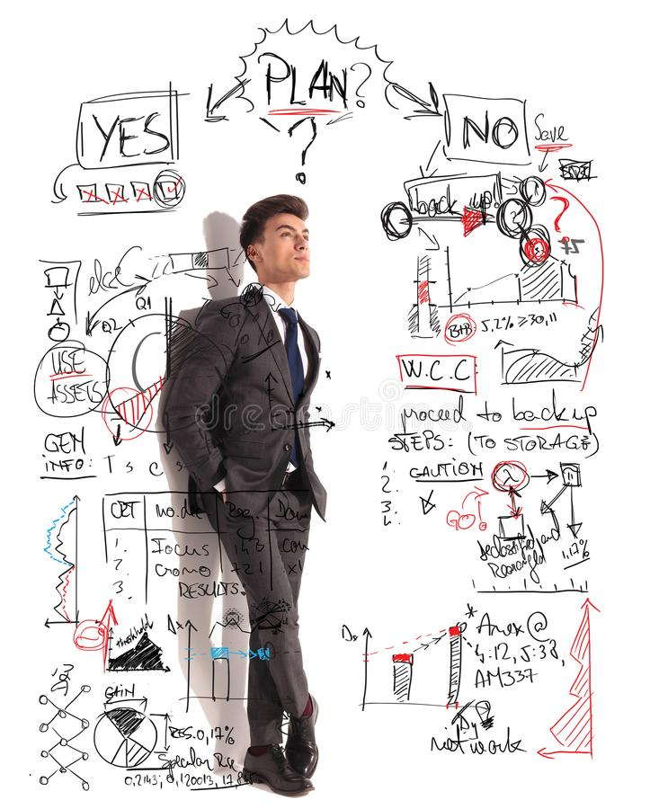 Business man trying to make the good decision. Young businessman with hands in pockets standing against a white wall and looks up to charts and diagrams of a royalty free stock photos