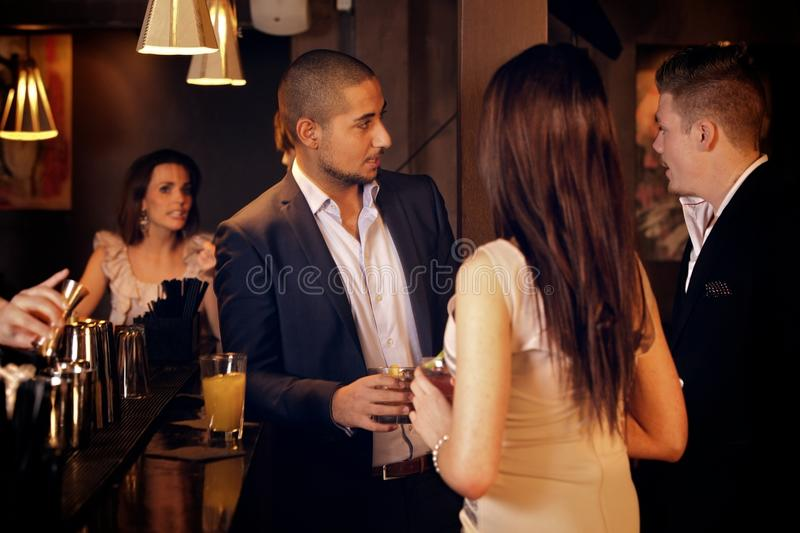 Young Businessman Hanging Out with Friends at the. Young businessman hanging out and talking with friends at the bar stock images