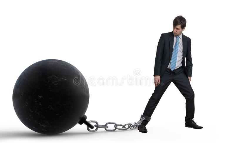 Young businessman has chained big metal ball to his leg. Isolated on white background. stock image