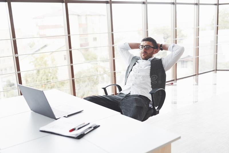 Young businessman having a rest while sitting in chair in the clean room and watching to the laptop royalty free stock photos