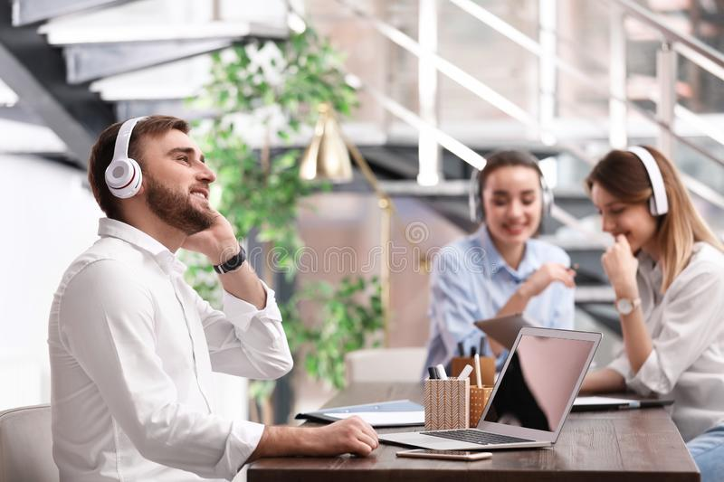 Young businessman with headphones, laptop and his colleagues at table. In office stock images
