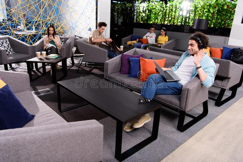 young businessman in headphones sitting on couch with laptop and waving by hand at modern coworking royalty free stock photo