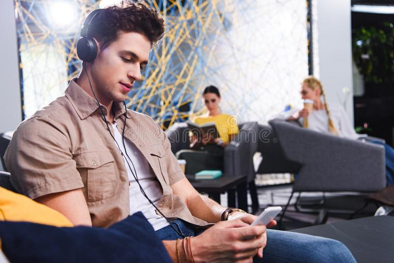 young businessman in headphones using smartphone at modern coworking royalty free stock image