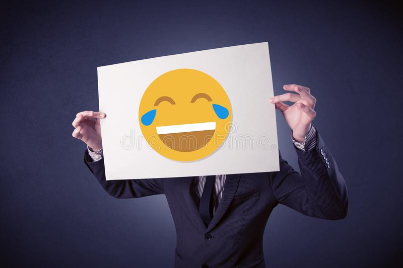 Businessman holding paper with laughing emoticon. Young businessman hiding behind a laughing emoticon on cardboard royalty free stock photography