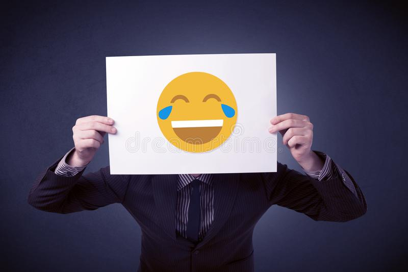 Businessman holding paper with laughing emoticon. Young businessman hiding behind a laughing emoticon on cardboard royalty free stock images