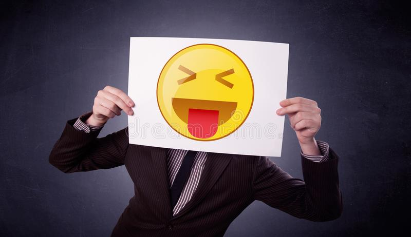 Businessman holding paper with emoticon. Young businessman hiding behind a playful emoticon on cardboard royalty free stock images