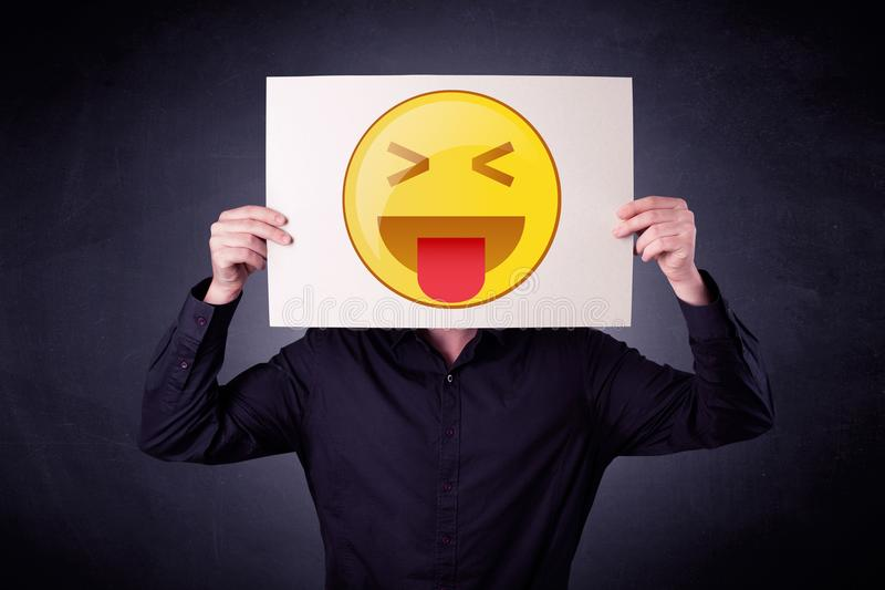 Businessman holding paper with emoticon. Young businessman hiding behind a playful emoticon on cardboard stock images