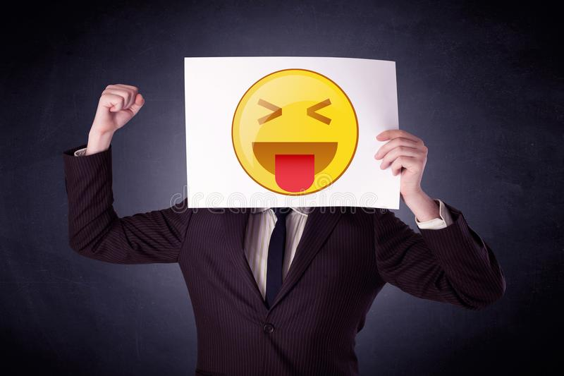 Businessman holding paper with emoticon. Young businessman hiding behind a playful emoticon on cardboard stock photography