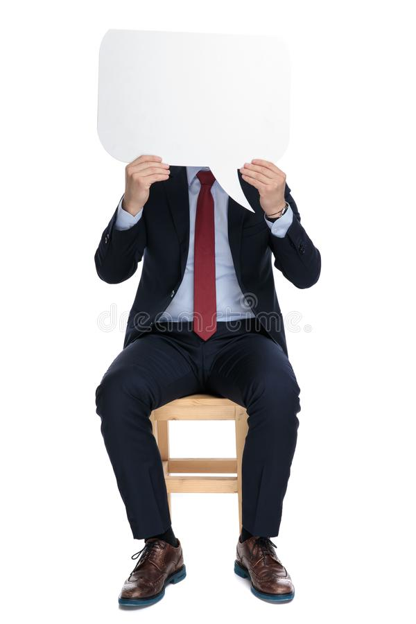 Young businessman hiding behind speech bubble royalty free stock photography