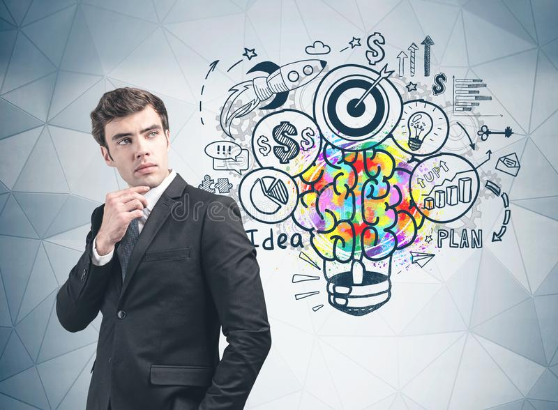 Young businessman and his business idea. Thoughtful young businessman standing near gray wall with colorful business idea sketch drawn on it. Concept of planning stock photography