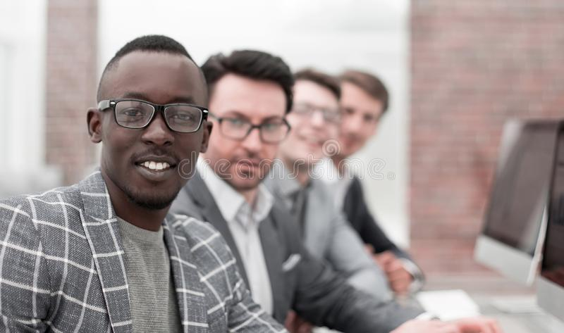 Young businessman and his business team sitting at the Desk stock images