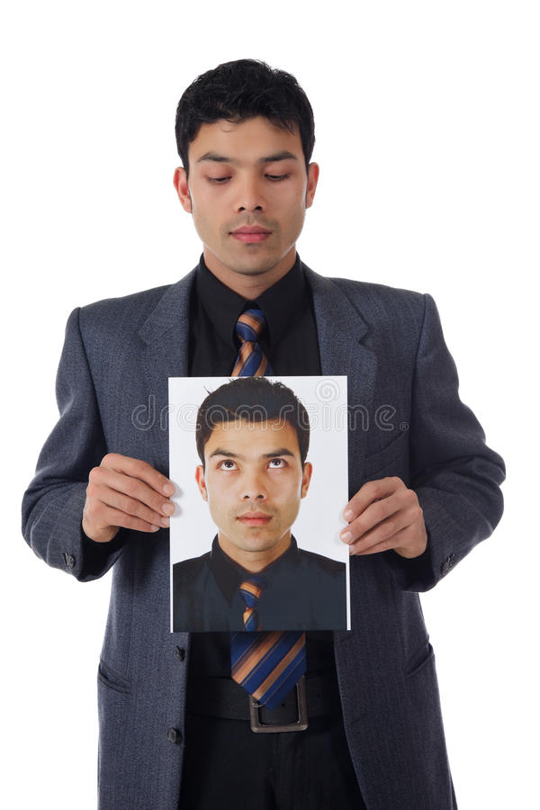 Young businessman and his consciousness. Young attractive nepalese businessman holding its own photo in hands and looking at. Point of conscience. Studio shot royalty free stock images