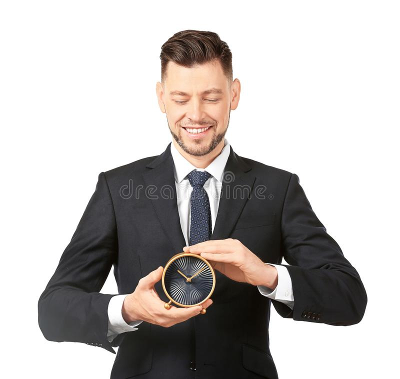 Young businessman holding alarm clock on white background stock photography