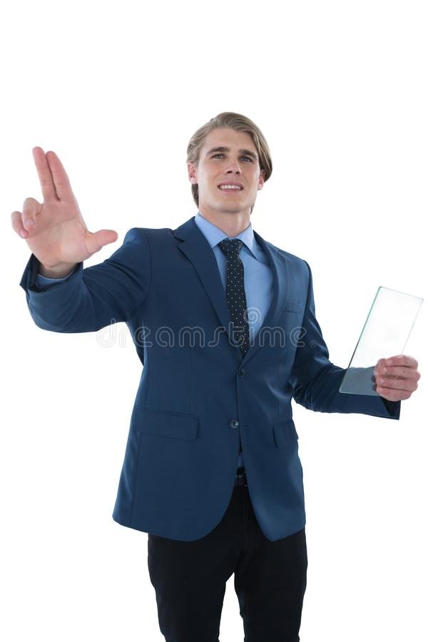 Young businessman holding glass interface while touching imaginary screen. Against white background royalty free stock photo