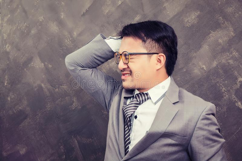 Young businessman holding hands on head so headache he got trouble with work. Background stock image