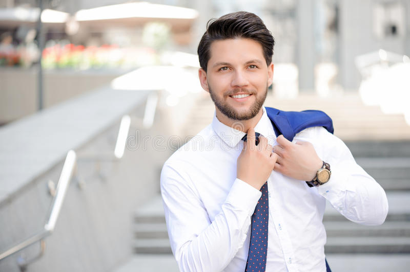 Young businessman holding jacket on shoulder royalty free stock image