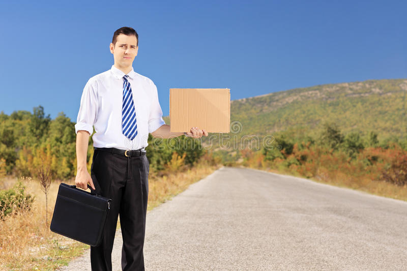 Young businessman holding a leather suitcase and hitchhiking royalty free stock photos