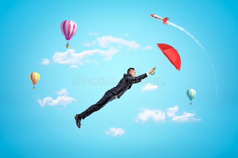 Young businessman holding red umbrella and flying up in blue sky, with hot air balloons and rocket in background. stock image