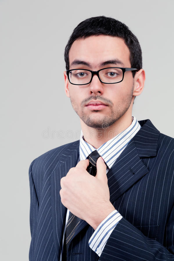 Young businessman holds tie stock photography
