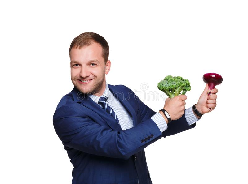 Young businessman holds vegetables, broccoli and red onion, isolated on white background. royalty free stock images