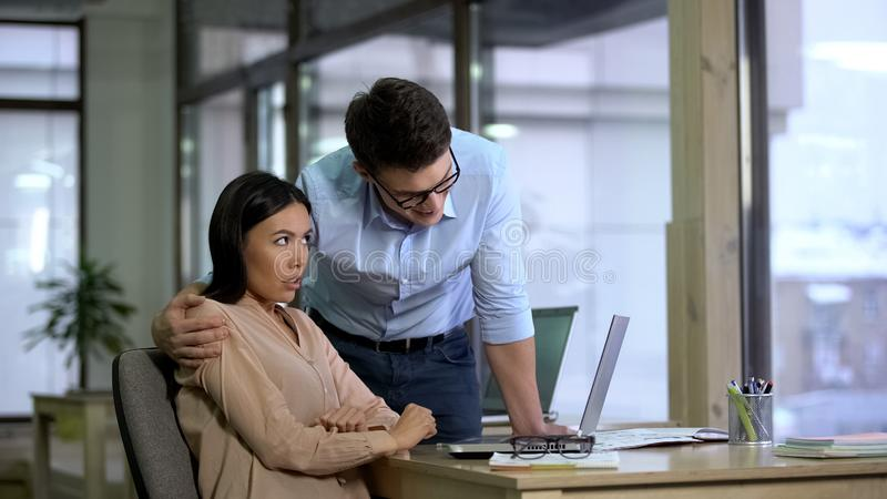Young businessman hugging beautiful female secretary, sexual harassment, abuse royalty free stock image