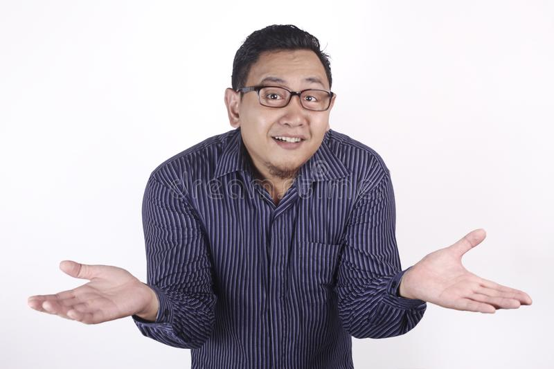 Young Businessman Indifferent Gesture. Young Asian businessman wearing blue shirt indefferent gesture. Close up body portrait indonesian malay thai chinese royalty free stock photo