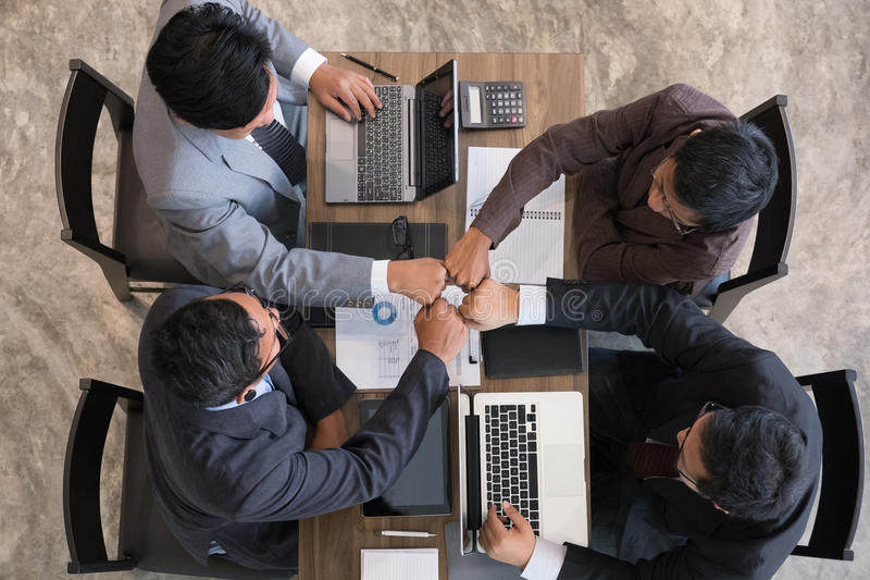 young businessman joining hand together, business team giving fist bump - unity, harmony, teamwork, partnership, collaboration, c stock image