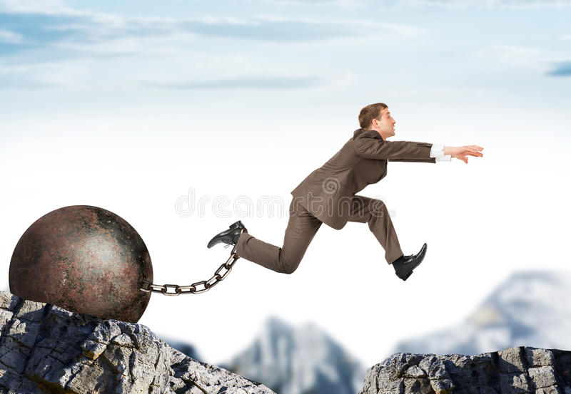 Young businessman jumping over gap royalty free stock photography
