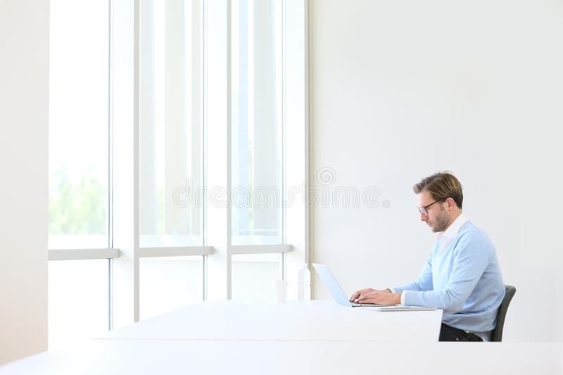 Young businessman on laptop isolated stock photography