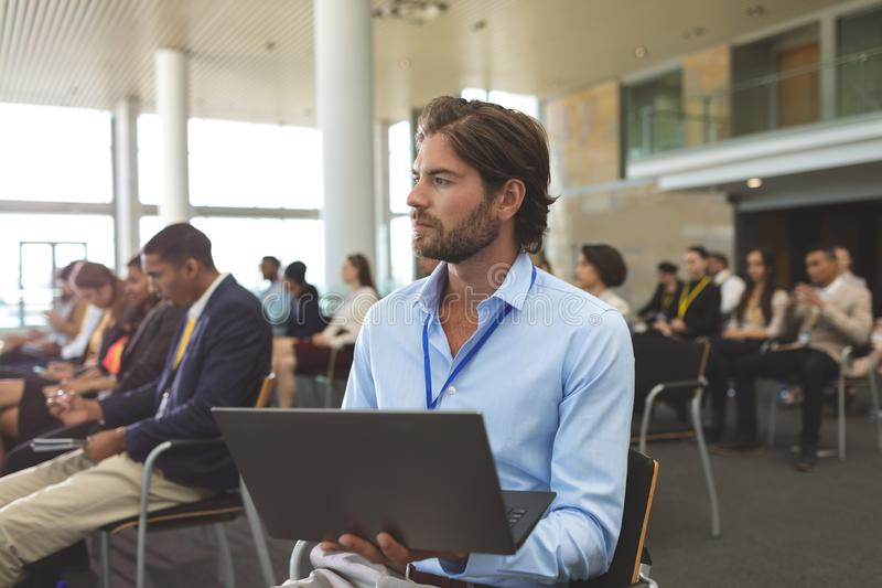 Young businessman with laptop looking away during seminar stock photography